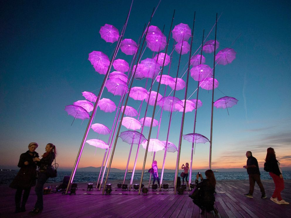 PHOTO: People stand around Umbrellas, the sculpture by Giorgos Zogolopoulos, as it is illuminated in pink light to mark Breast Cancer Awareness Month in Thessaloniki, Greece, Oct. 21, 2014.