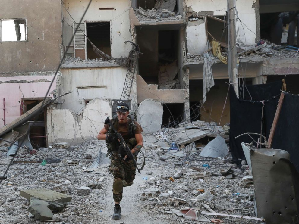 PHOTO: A U.S.-backed Syrian Democratic Forces fighter, runs in front of a damaged building as he crosses a street on the front line, in Raqqa city, Syria, July 27, 2017.