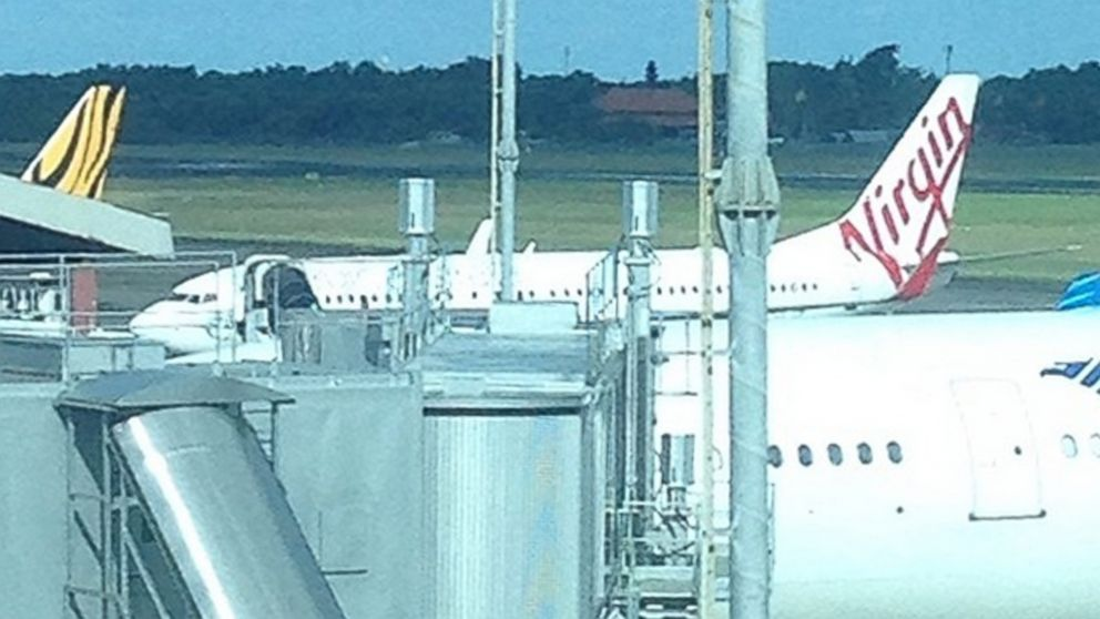 PHOTO: A Virgin Australia plane sits on the runway in Indonesia after airline officials said a passenger tried to break into the cockpit, April 25, 2014.