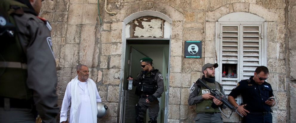 Israeli border police officers stand guard as Palestinians gather for prayer at the Lions Gate, following an appeal from clerics for Muslims to pray in the streets instead of the Al-Aqsa Mosque compound, in Jerusalems Old City, Wednesday, July 19,