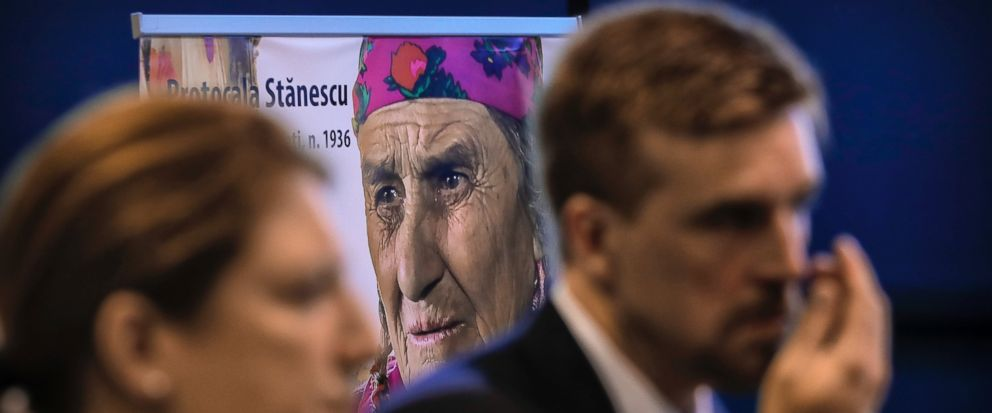 People attend a commemoration marking the extermination of thousands of Gypsies at a Nazi concentration camp, backdropped by the photograph of a survivor, in Bucharest, Romania, Wednesday, Aug. 2, 2017. Romanias foreign ministry said young generatio