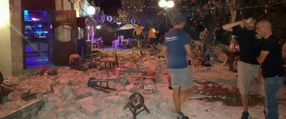 A man lies on the ground as other tourists stand outside a bar after an earthquake on the Greek island of Kos early Friday, July 21, 2017. A powerful earthquake struck Greek islands and Turkeys Aegean coast early Friday morning, damaging buildings a