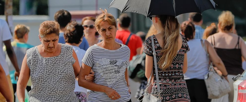 A girl uses an umbrella to shield herself from the sun in Bucharest, Romania, Friday, Aug. 4, 2017. Romanian meteorologists issued an extreme temperatures warning, with 42 Celsius (107.6 F) forecast for parts of western Romania and placing 12 countie