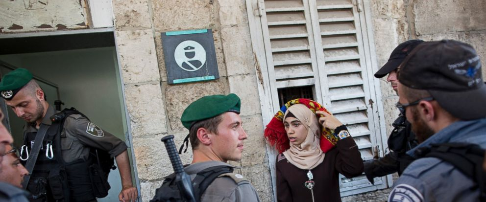 Israeli border police officers stop a Palestinian woman for a security check as Palestinians gather for prayer at the Lions Gate, following an appeal from clerics for Muslims to pray in the streets instead of the Al-Aqsa Mosque compound, in Jerusale