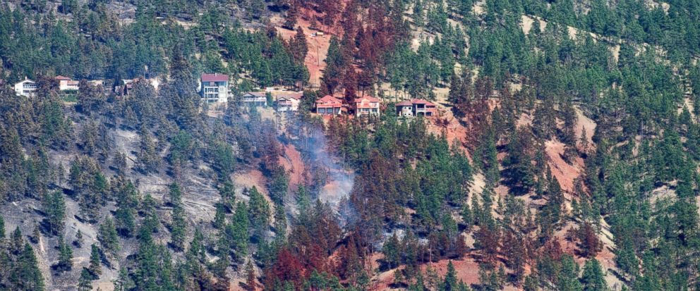 Smoke and fire retardant are seen along a neighborhood in Lake Country, British Columbia, Sunday, July 16, 2017. (Jonathan Hayward/The Canadian Press via AP)