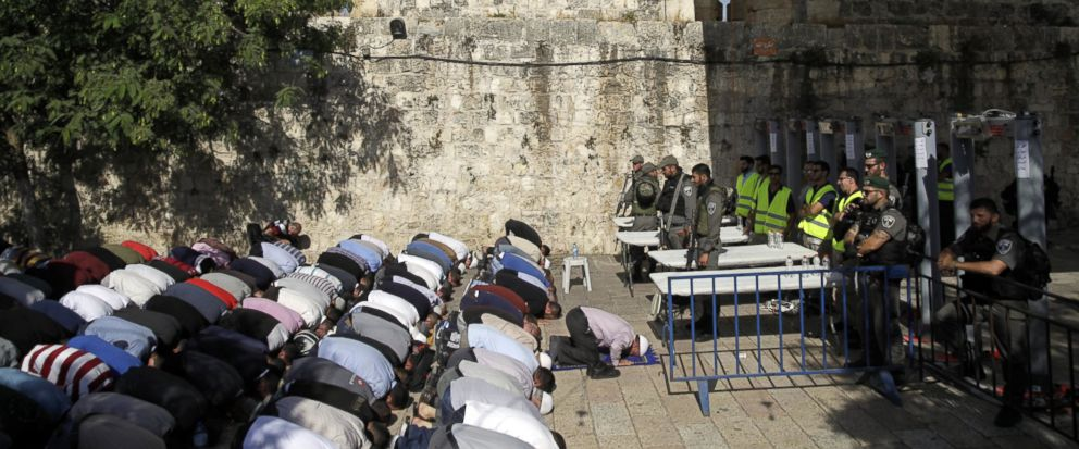 Israeli border police officers stand guard as Muslim men pray outside the Al Aqsa Mosque compound, in Jerusalem, Sunday, July 16, 2017. Adnan Husseini, the Palestinian Minister of Jerusalem, said Sunday that arrangements at the Muslim-administered ho