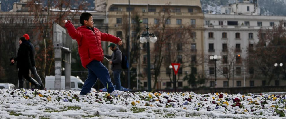 A boy winds up with a snowball in hand in a park in Santiago, Chile, Saturday, July 15, 2017. Record cold temperatures and an unusual snowfall hit Chiles capital Saturday. Normal temperatures are expected to return midweek. (AP Photo/Esteban Felix)