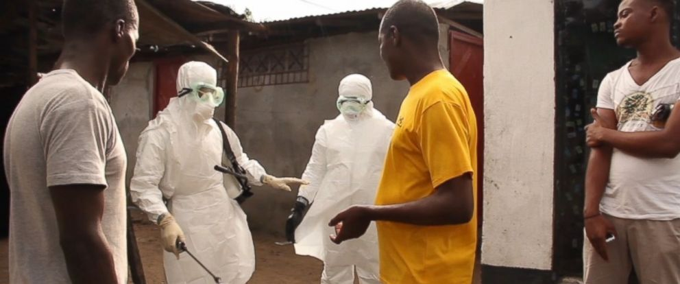 PHOTO: Liberian government health workers in hazmat suits met with residents of Clara Town in Liberia.