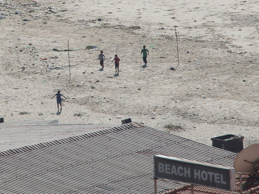 PHOTO: Four boys sprint across a beach in Gaza after the first blast from an Israeli shell.