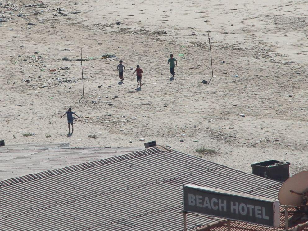 PHOTO: Four boys sprint across a beach in Gaza after the first blast from an Israeli shell.