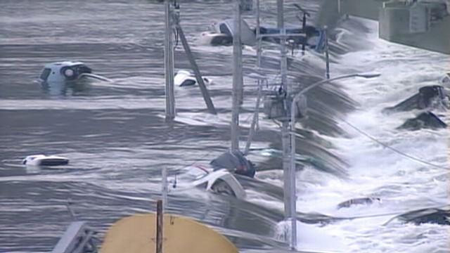 VIDEO: Surging waters sweep vehicles under a road bridge in Miyagi Prefecture, Japan.