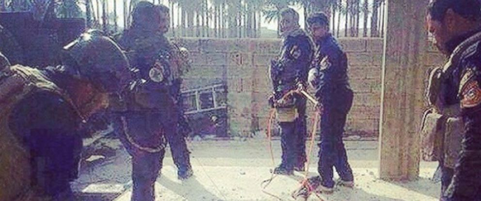 """PHOTO: In an image posted on Instagram, six black-uniformed men who appear to be Iraqi Special Operations Forces from the """"Golden Brigades"""" surround an alleged ISIS suspect who has been dragged with a rope or cable tied to his foot."""