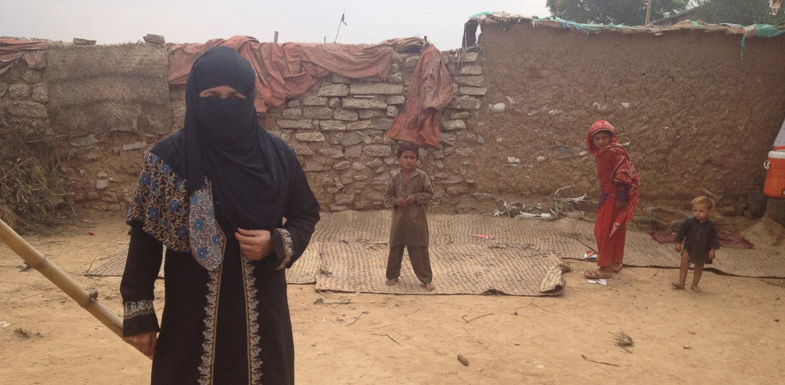 PHOTO: Chand Bibi at school with some of her students in the background. Her school has no roof, a limited number of notebooks and a tiny white board, but she thinks it provides some service for children who would otherwise have no school to go to.