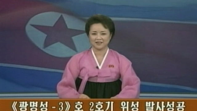 PHOTO: An unnamed television presenter announces the successful launch of an n intercontinental ballistic missile.