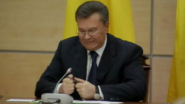 Viktor Yanukovich attempts to break his pen in half before delivering a message to the Ukrainian people.