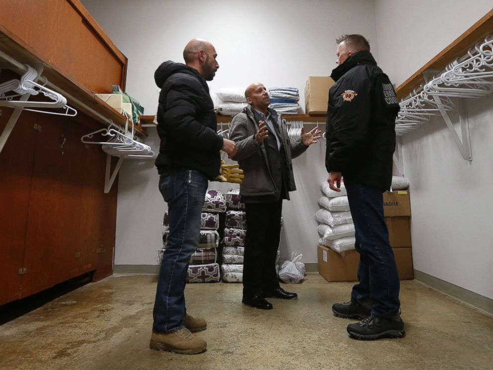PHOTO: Fadel Alshawwa and Jean Pierre Venegas talk with Bill Spanjer, Municipal Emergency Coordinator for Emerson-Franklin, talk as they bring blankets and pillows into a community hall for refugees that may walk across the border in Emerson, Manitoba.