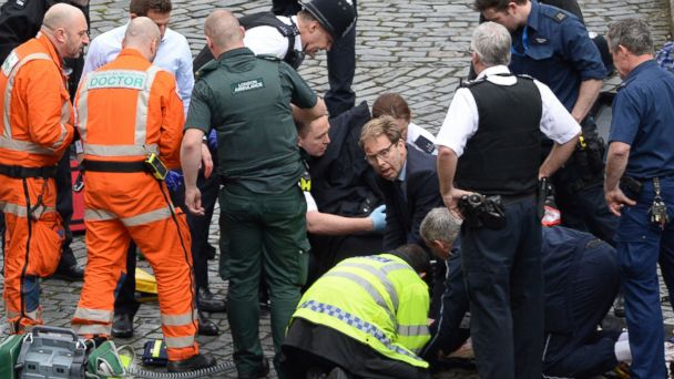 PHOTO: Conservative Member of Parliament Tobias Ellwood, center, helps emergency services attend to an injured person outside the Houses of Parliament, London, March 22, 2017.