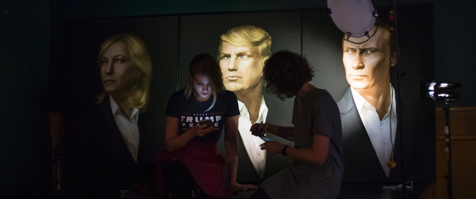 PHOTO: Two women look at their cell phones in front of portraits of U.S. President-elect Donald Trump and Russian President Vladimir Putin, right,at the Union Jack pub in Moscow to watch a live telecast of the U.S. presidential election, Nov. 9, 2016.