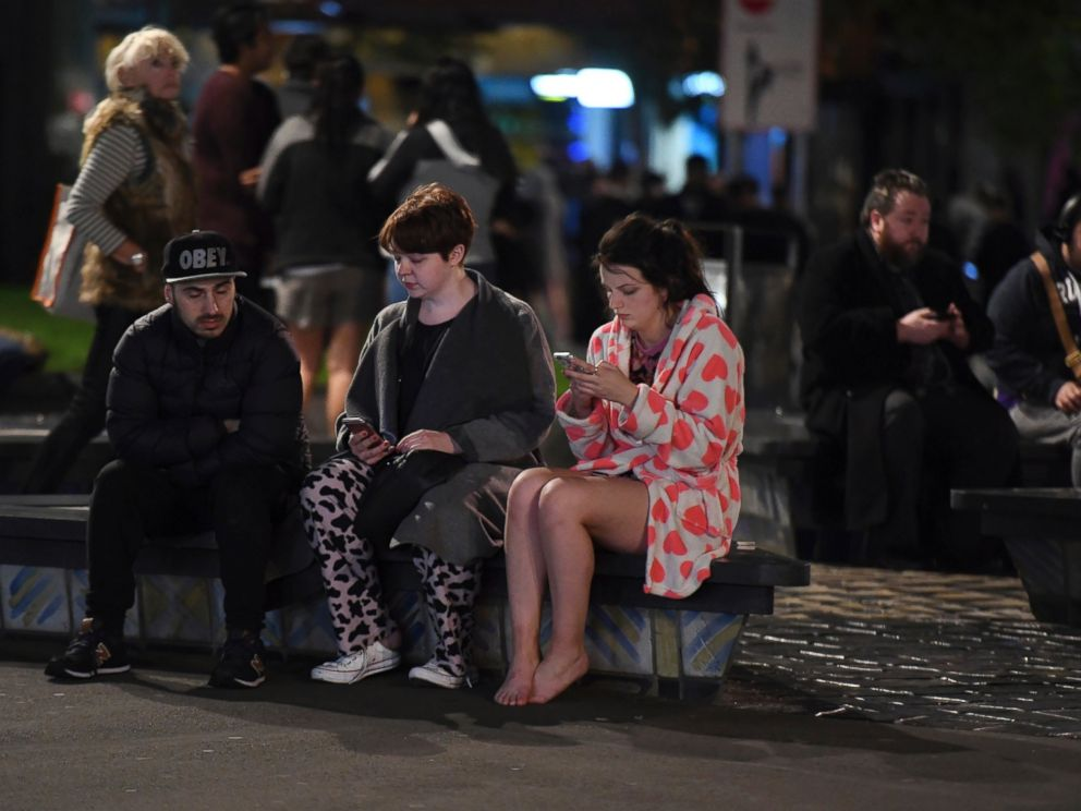 PHOTO: People evacuated from buildings along Dixon Street check their mobile phones while sitting on a bench in Wellington, New Zealand, after a 6.6 earthquake, Nov. 14, 2016.