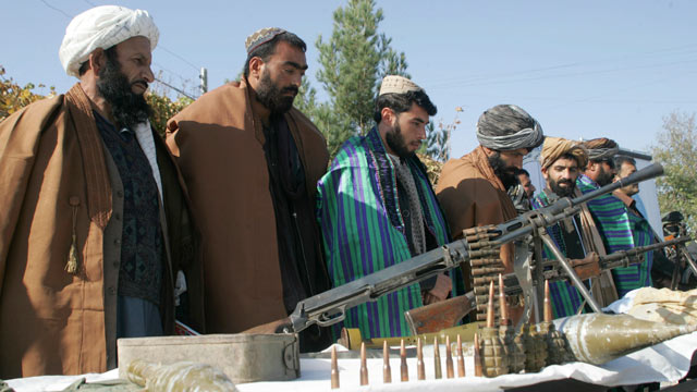 PHOTO: Taliban fighters line up as they hand over their weapons to join the peace process i