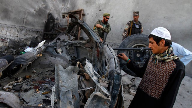 PHOTO: An Afghan man examines the remains of a car after three suicide bombers were killed before they reached Jalalabad airport, which security forces say was their target, in Jalalabad, east of Kabul, Afghanistan on Sunday, April 15, 15 2012.
