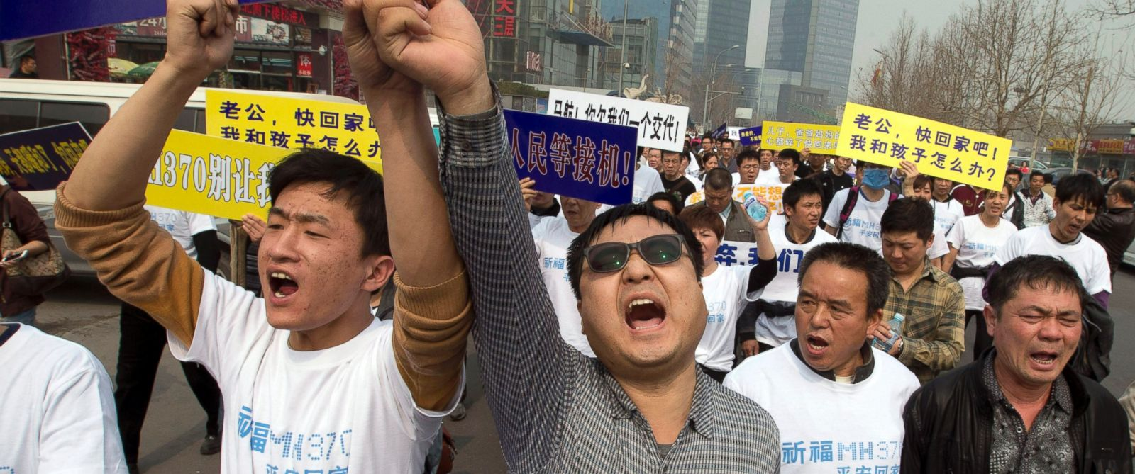 PHOTO: Chinese relatives of passengers aboard the missing Malaysia Airlines plane, flight MH370, shout in protest as they march towards the Malaysia embassy in Beijing, China, Tuesday, March 25, 2014.