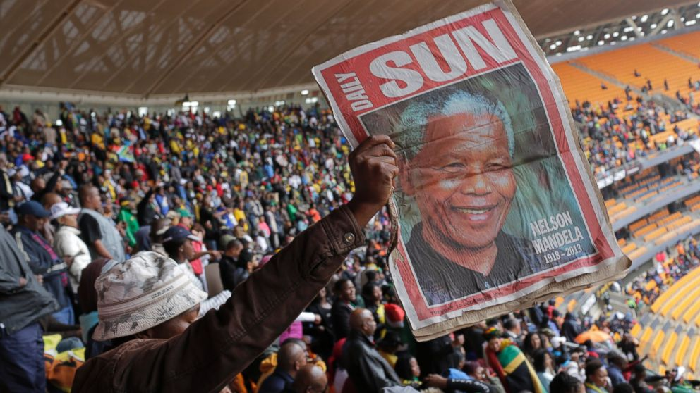 PHOTO: A man holds up an image of former South African president Nelson Mandela ahead of a memorial service at the FNB Stadium in Soweto, near Johannesburg, South Africa, Tuesday Dec. 10, 2013.