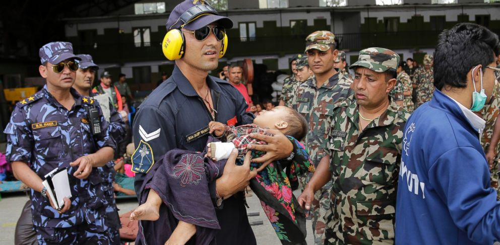 PHOTO: A member of the Indian Air Force carries a Nepalese child, wounded in Saturdays earthquake, to a waiting ambulance after the child and mother were evacuated from a remote area at the airport in Kathmandu, Nepal, April 27, 2015.