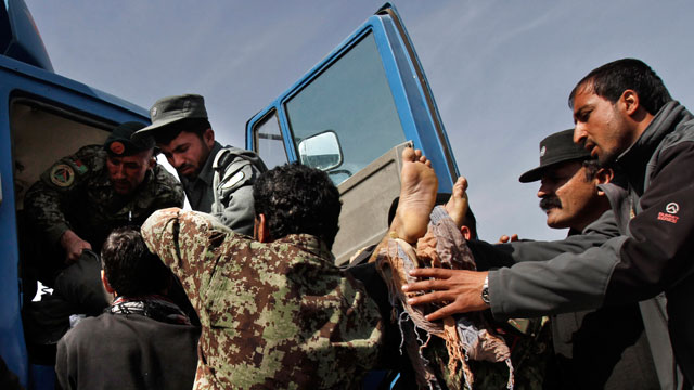 PHOTO: Afghan Army soldiers remove a dead passenger from a truck after U.S. forces shot at an Afghan truck, killing two passengers and injuring another on the road between Kabul and Bagram, Afghanistan, March 11, 2013.