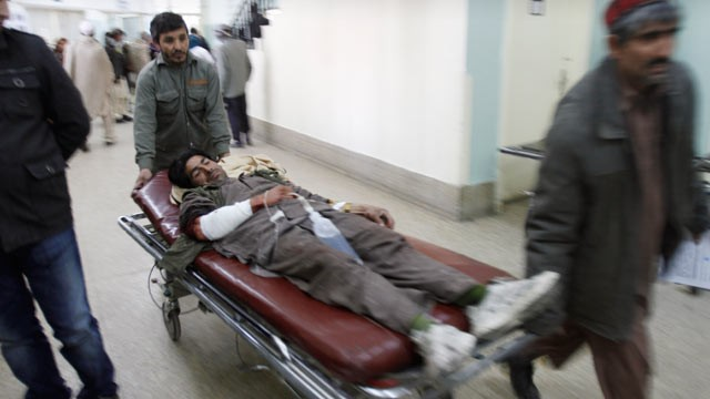 An Afghan man wounded during an anti-US demonstration is wheeled into a hospital in Kabul, Afghanistan Feb. 22, 2012
