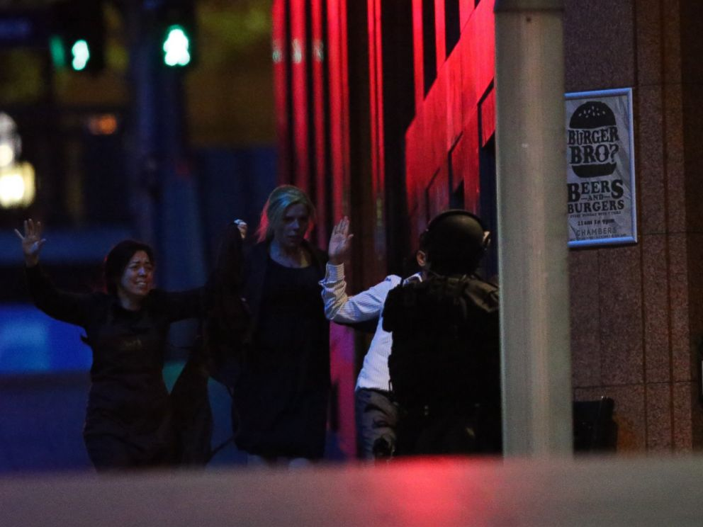 PHOTO: Hostages run towards armed tactical response police as they run to freedom from a cafe under siege at Martin Place in the central business district of Sydney, Australia, Dec. 16, 2014.