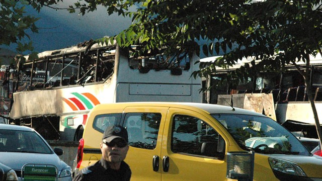 PHOTO:&nbsp;Bulgarian policeman is seen in front of destroyed buses at Burgas Airport, outside the Black Sea city of Burgas, Bulgaria, Wednesday, July 18, 2012.