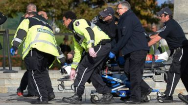 PHOTO: Paramedics and police pull a victim away from the Canadian War Memorial in Ottawa, Canada, Oct. 22, 2014.