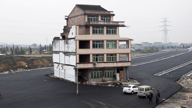 PHOTO: In this Nov. 22, 2012 file photo, people stand near a house sitting in the middle of a new main road on the outskirts of Wenling city in east China's Zhejiang province.