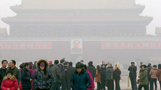 PHOTO: Visitors stand on Tiananmen Square across from a portrait of former Chinese leader Mao Zedong in thick haze in Beijing, China, Jan. 29, 2013.