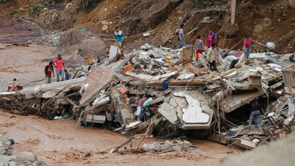 PHOTO: People walk over the debris of a collapsed building in Mocoa, Colombia, Sunday, April 2, 2017. Colombia's President Juan Manuel Santos declared Mocoa a disaster area.