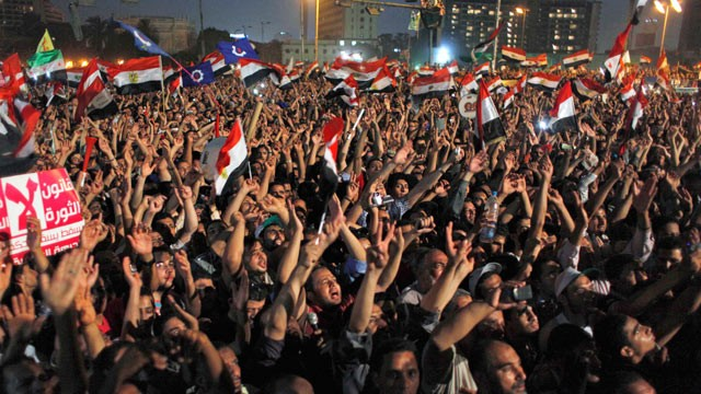 "PHOTO: Egyptian Muslim Brotherhood supporters wave national flags and chant slogans, and one carries a banner that reads in Arabic ""The law of the revolution not the law military,"" during an anti-ruling military council demonstration in Tahrir Square, Cai"