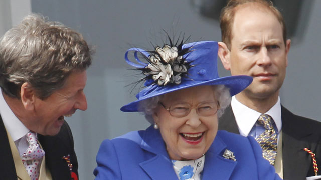 PHOTO: Britains Queen Elizabeth II, center, reacts as she looks out from the balcony at the end of the Epsom Derby horse race at Epsom racecourse England at the start of a four-day Diamond Jubilee celebration