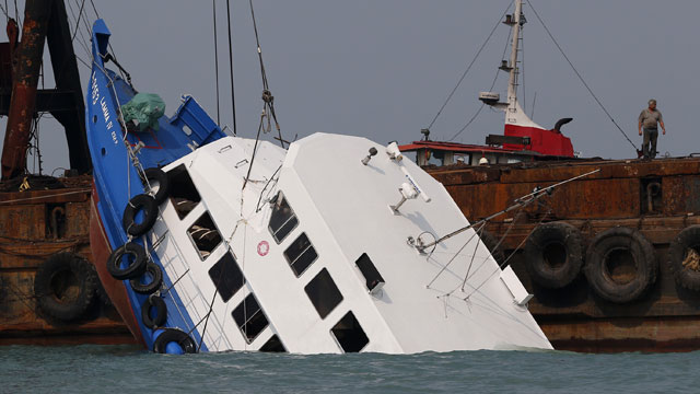 PHOTO: Officials check on a half submerged boat after it collided Monday night near Lamma Island, off the southwestern coast of Hong Kong Island Tuesday Oct. 2, 2012.