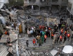 PHOTO: Palestinians stand in the rubble of the Daloo family house following an Israeli air strike in Gaza City, Nov. 18, 2012.