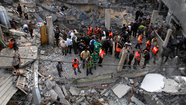 PHOTO: Palestinians stand in the rubble of the Daloo family ho