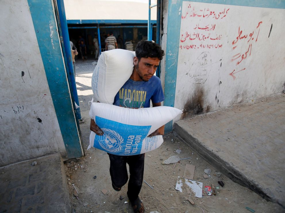 PHOTO: A Palestinian carries bags of flour at a United Nations food aid distribution center, in Shati refugee camp in Gaza City, Aug. 6, 2014.
