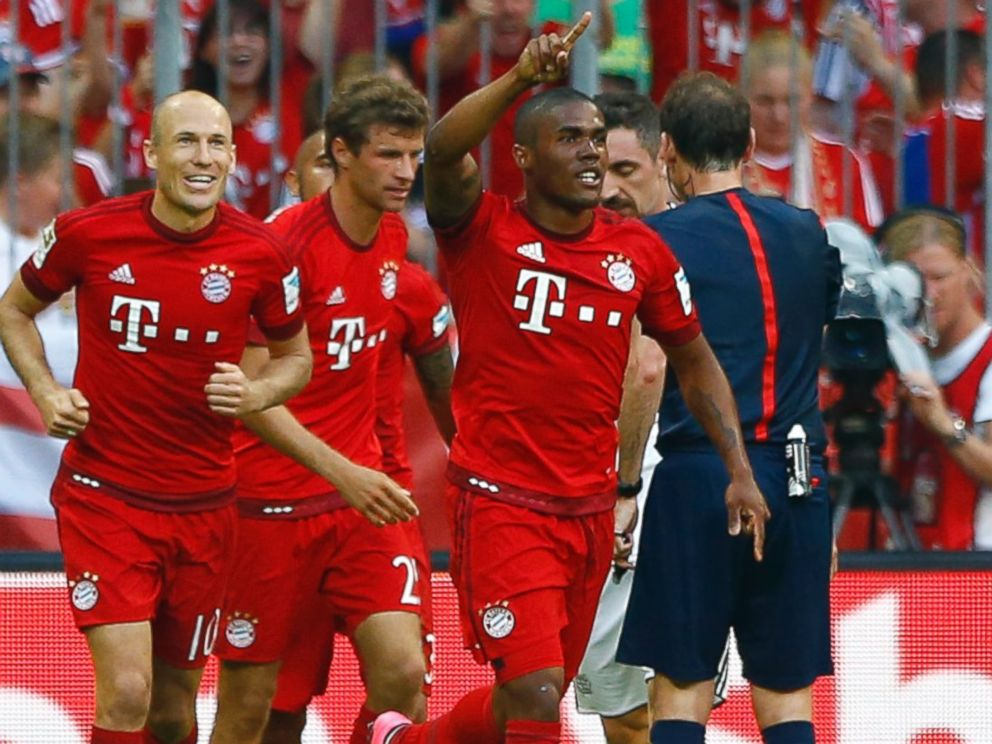 PHOTO: Bayerns Douglas Costa celebrates after teammate Thomas Mueller, scored his sides opening goal during the German Bundesliga soccer match between FC Bayern Munich and Bayer Leverkusen in Munich, Germany, Aug. 29, 2015.
