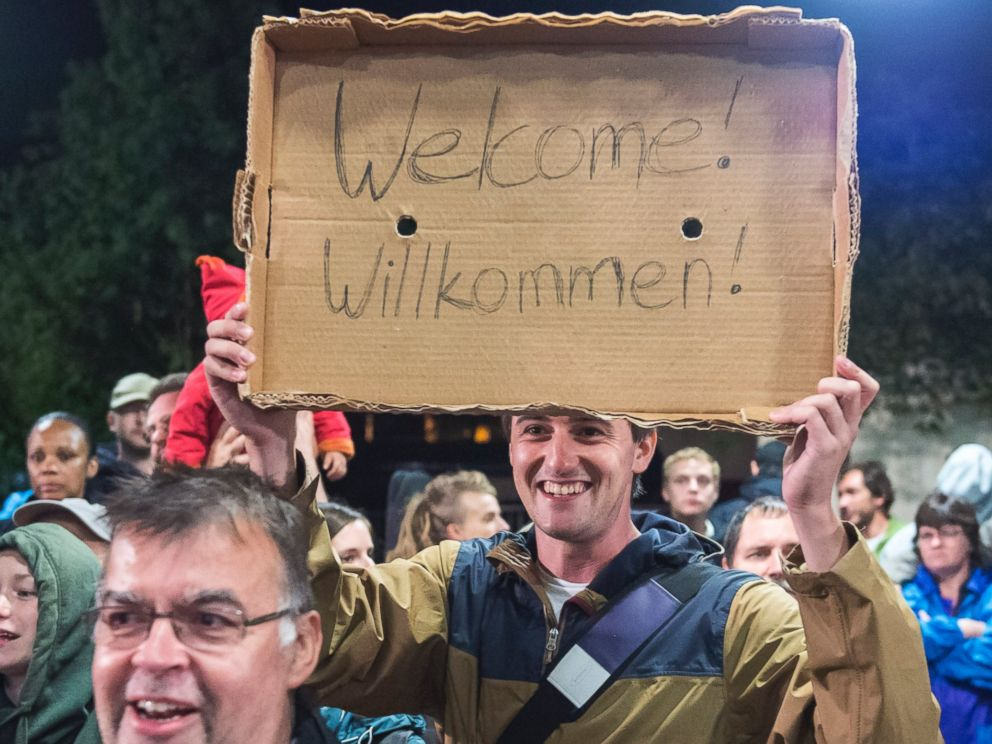 PHOTO: A man holds a Welcome sign for arriving refugees at the train station in Saalfeld, central Germany, Sept. 5, 2015.