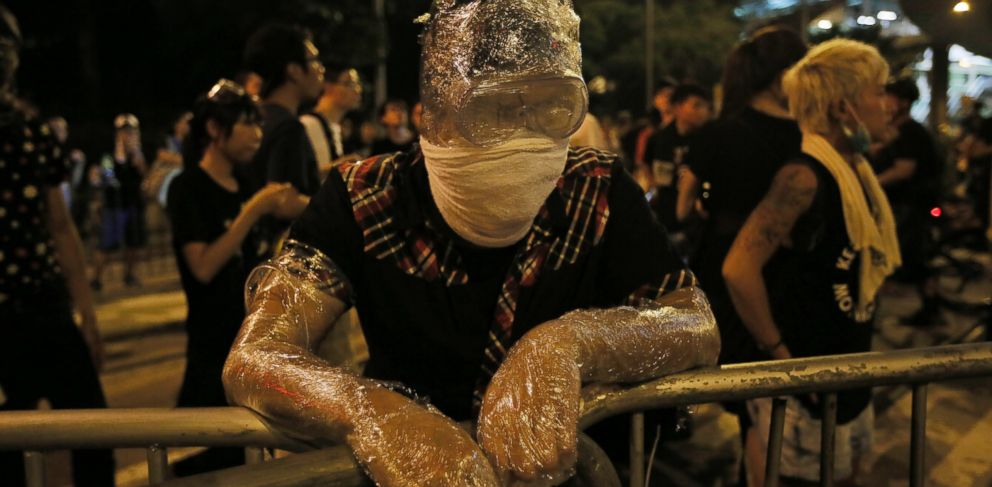 PHOTO: Wrapped in plastic to shield from pepper spray, a student protester stands behind a makeshift barrier blocking main streets in the central business district of Hong Kong, late Monday, Sept. 29, 2014.