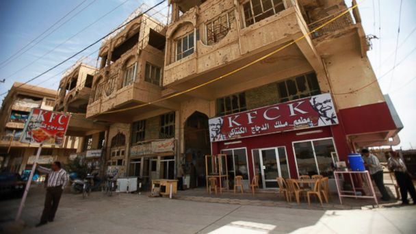 "PHOTO: A man stands in front of a new chicken restaurant ""King of Kentucky Chicken Restaurant,"" with two large images of Colonel Sanders in Fallujah, Iraq on March 23, 2009."