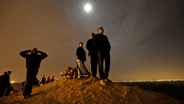 PHOTO: The moon illuminates Israelis standing on a hill at the Israeli town of Sderot, overlooking the Gaza Strip, as they watch a missile, not seen, fired by Palestinian militants from inside Gaza towards southern Israel, Nov. 21, 2012, shortly before a