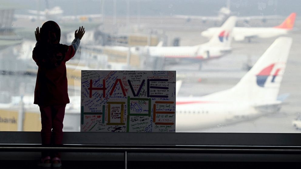 PHOTO: A girl stands next to a sign board made and written by the public at Kuala Lumpur International Airport in Sepang, Malaysia, March 10, 2014.