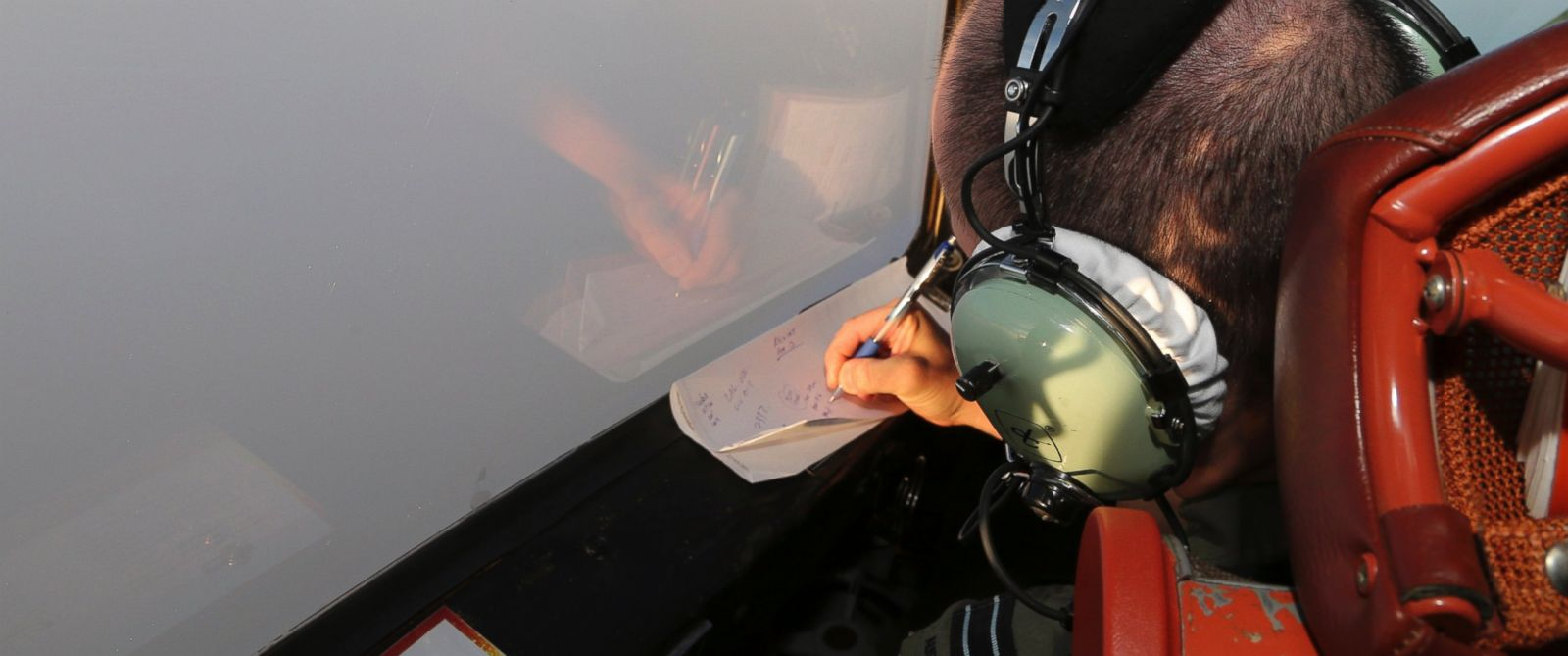 PHOTO: Flight Lt. Jason Nichols on board a Royal Australian Air Force AP-3C Orion, takes notes as they search for the missing Malaysia Airlines Flight MH370 in southern Indian Ocean, Australia, Saturday, March 22, 2014.