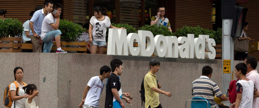 PHOTO: Pedestrians pass by a McDonalds restaurant in Beijing, July 22, 2014.